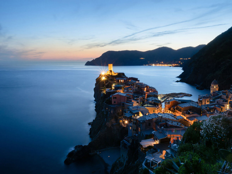 stunning blue hour landscape photo of houses and the ocean with coastline in the distance showing the colors of sunset
