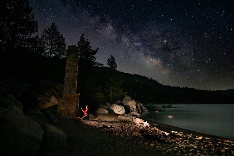 Light painting at Lake Tahoe beach at night with stars in the sky