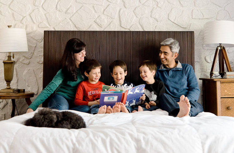 self portrait of family in bed reading books to the kids