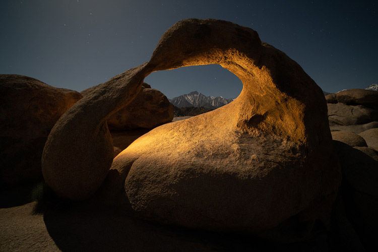 night photo of same stone arch but with a small light source illuminating it for effect