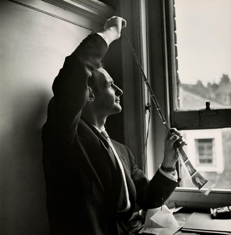 black and white photo of famous portrait photographer Irving Penn reviewing a strip of negatives
