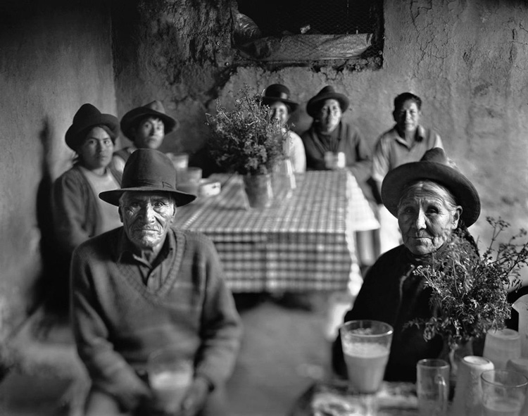 classic portrait of a Peruvian family as they sit in their dining room wearing traditional clothes, taken using a large format camera