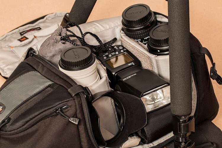camera bag with photography gear inside, showing lenses, flash and tripod