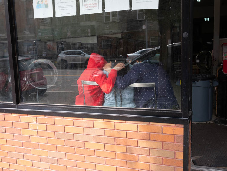 group of people inside laundromat through window before editing